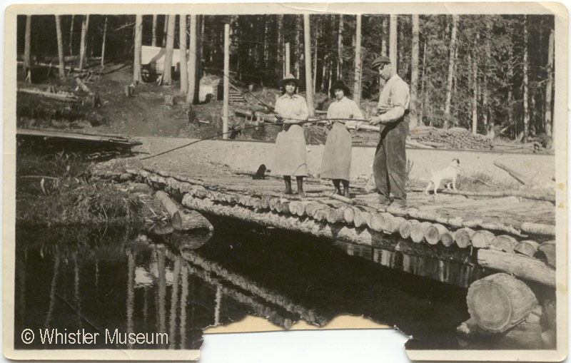 Margaret Tapley, Edna, & her husband Don McRae with dog Ki, fishing from the log bridge to Tracks, Myrtle's tent house. 1915. Inscription reads: Rainbow 1915. Philip Collection.