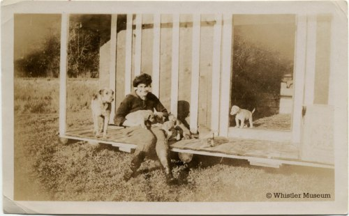 Myrtle Philip sitting with dog and puppies, ca. 1930. Philip Collection.
