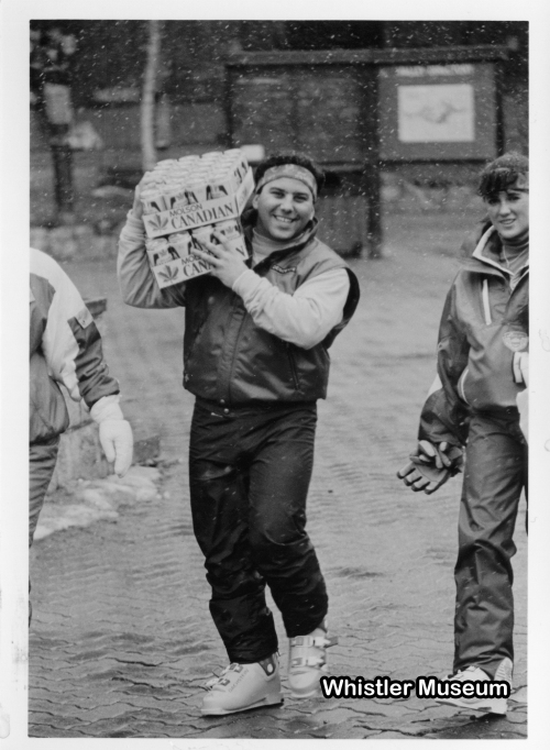 A man, still in his ski boots, carries two flats of 'Canadian' beer on his shoulders, fittingly a huge grin is spread across his face.
