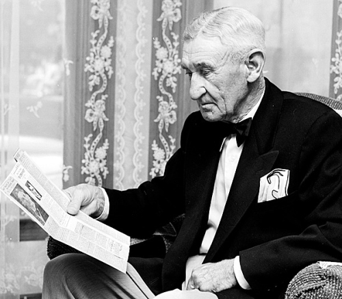 Alex Philip, Blue Hill native, popular Bangor counterman and successful British Columbia resort owner, is shown looking over a Bangor Daily News clipping which detailed his departure from Bangor in 1906.  Mr. Philips returned to visit Bangor in August 1956. BANGOR DAILY NEWS FILE PHOTO BY SPIKE WEBB