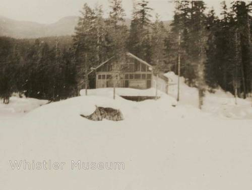 This photograph shows a house on a point at Alpha Lake during wintertime. The house is almost certainly that of Dr. & Grace Naismith. Annotations in pen on the reverse of the image read: