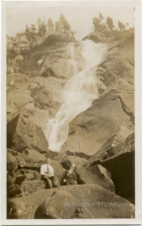 Alex Philip and friend in suits and ties, sitting at the base of Shannon Falls, circa 1920.