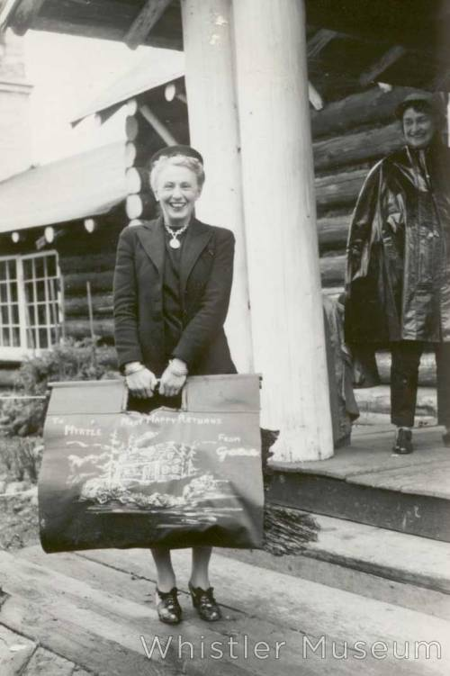 Grace Naismith at Rainbow Lodge holding a wood carrier inscribed